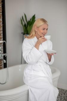 Poranna kawa. kobieta w białej szacie pijąca poranną kawę i wyglądająca na zadowoloną