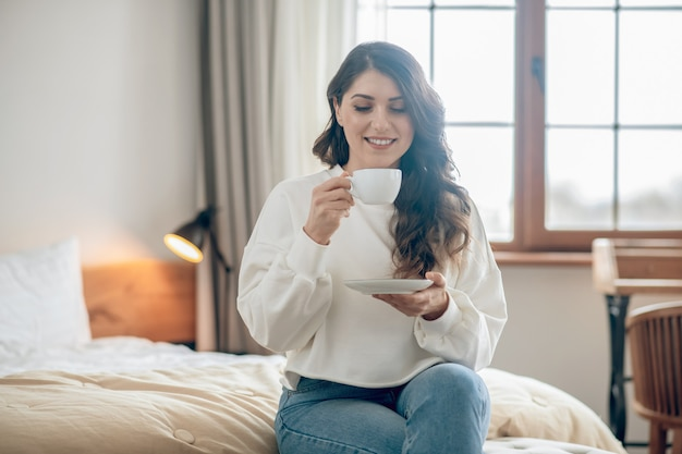 Poranna kawa. ładna młoda kobieta siedzi na łóżku i pije kawę