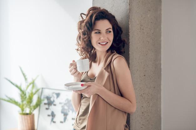 Poranna kawa. młoda uśmiechnięta kobieta o kawie rano