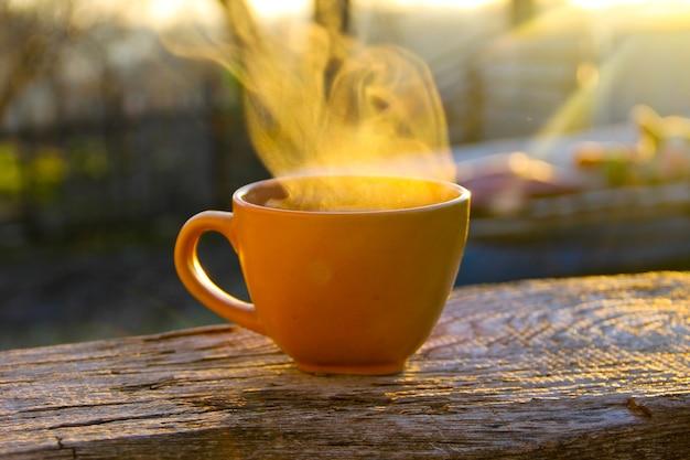 Poranna kawa na drewnianym stole o wschodzie słońca