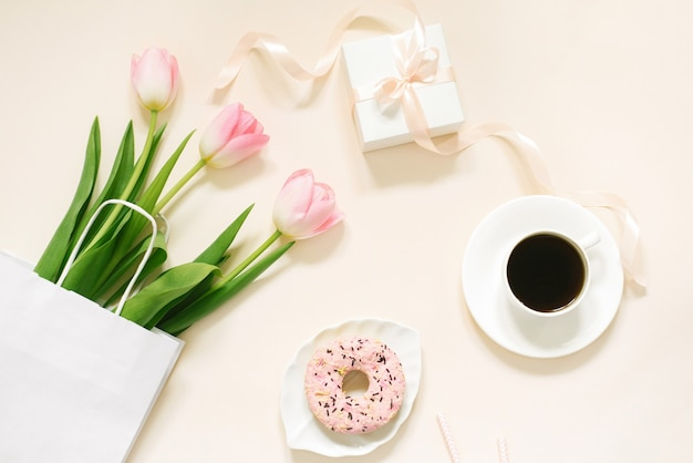 Poranna kawa, pączek, prezent lub teraźniejszość pole i wiosenne kwiaty tulipanów na beżowym tle. piękne śniadanie na dzień kobiet, dzień matki, walentynki. leżał płasko.