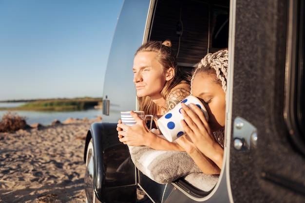 Poranna kawa. para przystojnych podróżników pije poranną kawę po nocy w przyczepie stacjonarnej