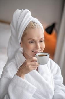 Poranna kawa. piękna kobieta w białej szacie pijąca kawę po kąpieli