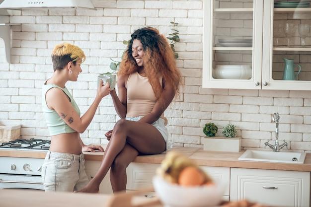 Poranna kawa. radosna ciemnoskóra kobieta w szortach boso siedzi na kuchennym stole swojej dziewczyny w dżinsach stojącej obok kawy
