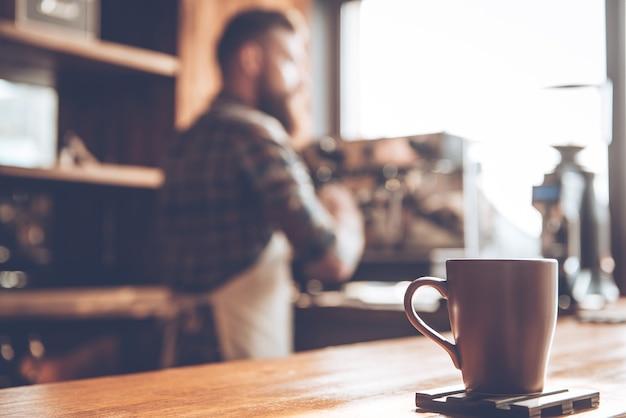 Poranna kawa. skoncentrowany obraz filiżanki kawy stojącej przy barze z młodym brodatym mężczyzną w fartuchu robiącym kawę w tle