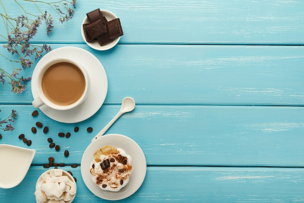 Poranna kawa tło. border cappuccino cup, słoik mleka, czekolada, małe ciastka i rafinowany cukier na niebieskim rustykalnym drewnianym stole, miejsce na kopię, widok z góry