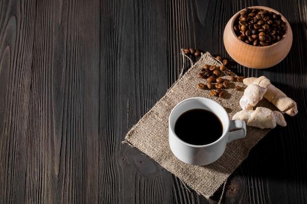 Poranna kawa w białej filiżance, ciasteczka czekoladowe na drewnianym tle