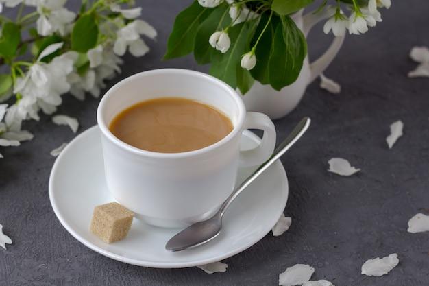 Poranna kawa w słoneczny dzień. wiosenna kompozycja, kawa z mlekiem na śniadanie wśród świeżych wiosennych kwiatów.
