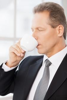 Poranna kawa. widok z boku dojrzałego mężczyzny w stroju formalnym pijącego kawę i trzymającego oczy zamknięte