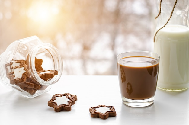 Poranna kawa z mlekiem i czekoladowymi ciastkami lub ciastkami w kształcie gwiazdy na widoku z okna