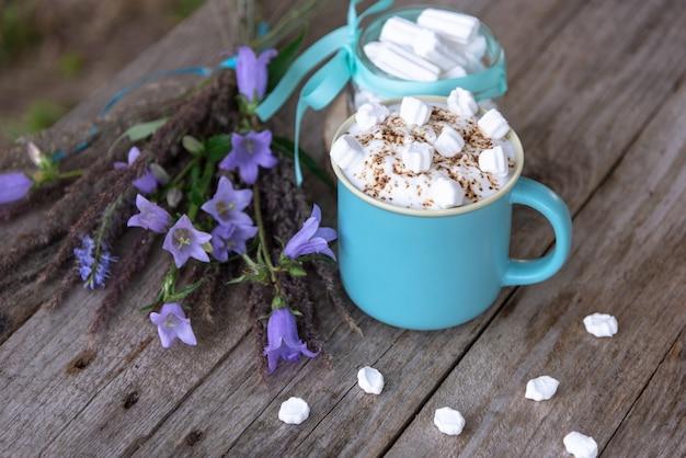 Poranna kawa z pianką i piankami na drewnianej przestrzeni z kwiatami bzu.