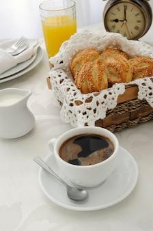 Poranna kawa ze świeżo upieczonymi bułeczkami z sezamem, sokiem i mlekiem