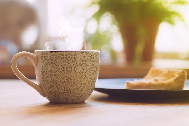 Poranną kawę zz szarlotką na drewnianym stole. koncepcja porannej kawy