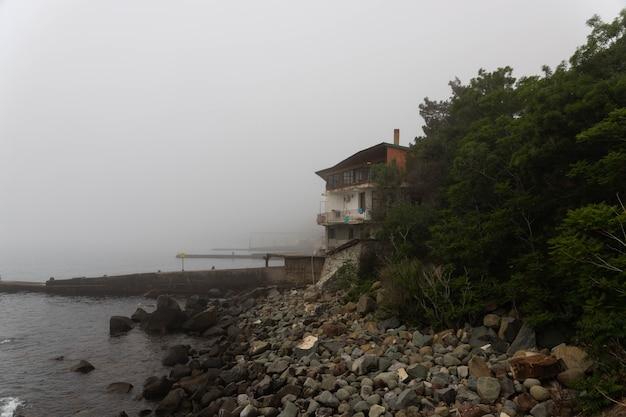 Poranna mgła nad brzegiem z domem w pobliżu morza czarnego.