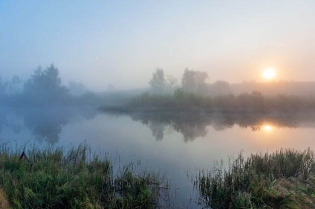 Poranna mgła nad jeziorem w godzinach porannych. piękny letni krajobraz
