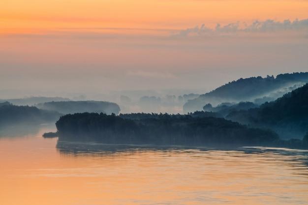 Poranna mistyczna mgła nad szeroką doliną rzeki. złoty blask od świtu na niebie. brzeg rzeki z lasem pod mgłą. światło słoneczne odbite w wodzie o wschodzie słońca. kolorowy klimatyczny krajobraz majestatycznej przyrody.