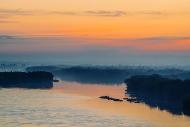 Poranna mistyczna mgła nad szeroką doliną rzeki. złoty blask od świtu na niebie.