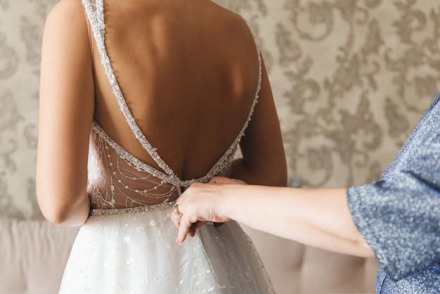 Poranna panna młoda. druhna pomaga pannie młodej sznurować sukienkę. dziewczyny pomagają pannie młodej zapiąć sukienkę