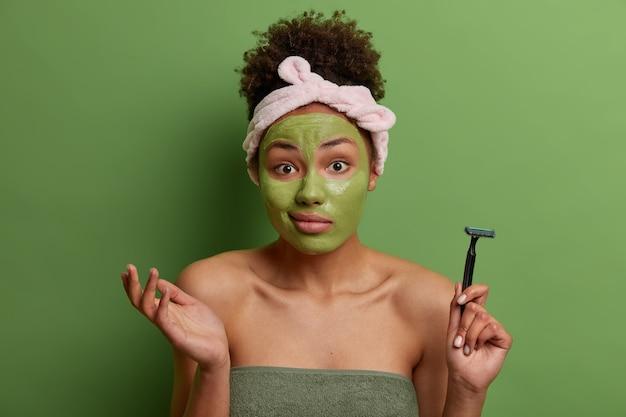 Poranna pielęgnacja skóry. nieświadoma kobieta z wahaniem wzrusza ramionami, nakłada maskę nawilżającą na twarz, trzyma brzytwę do golenia, zawinięta w ręcznik kąpielowy, pozuje przy jaskrawozielonej ścianie