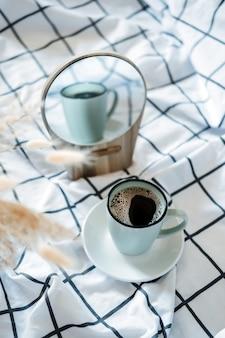 Poranna przytulna kawa w łóżku filiżanka czarnej kawy w łóżku na białym kocu w kratkę