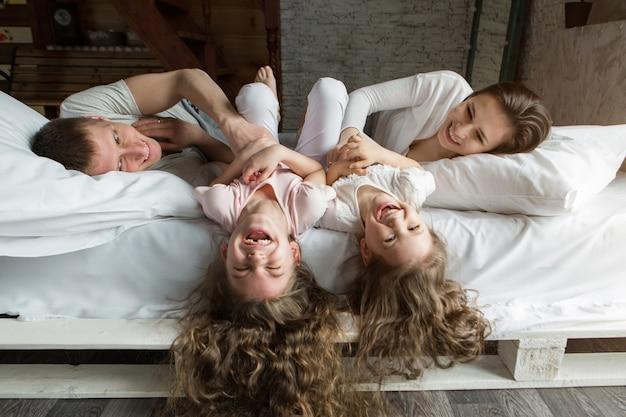 Poranna rodzina: dzieci bawiące się w łóżku z rodzicami. budząc się ze snu. właśnie się obudziłem. kocham