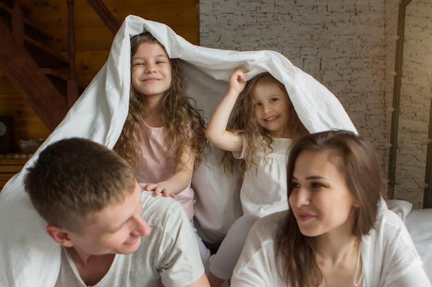 Poranna rodzina dzieci z rodzicami bawiące się w łóżku budząc się ze snu właśnie obudziłem miłość