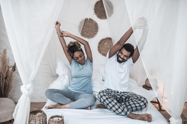 Poranna rozgrzewka. wesoły ciemnoskóry mężczyzna i kobieta w piżamie budzą się, rozciągając się, siedząc na łóżku rano