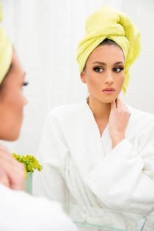 Poranna rutyna koncepcja, nowoczesny styl życia. kobieta patrząc na swoje odbicie w lustrze, w łazience na sobie szlafrok i ręcznik.