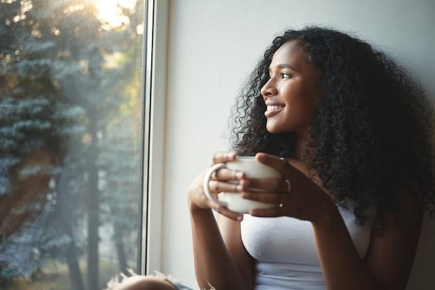 Poranna rutyna. portret szczęśliwa urocza młoda kobieta rasy mieszanej z falującymi włosami, ciesząc się letnim widokiem przez okno, pijąc dobrą kawę, siedząc na parapecie i uśmiechając się. piękny marzyciel