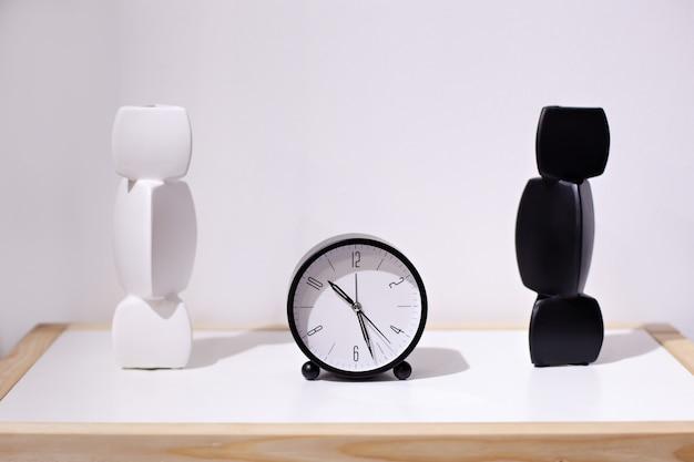 Poranna ściana czasu, budzik w pobliżu łóżka w domu. klasyczny budzik i dwie wazony w czerni i bieli. biurko widokowe z okrągłym czarnym zegarem z ceramicznym wazonem na białej ścianie. minimalizm