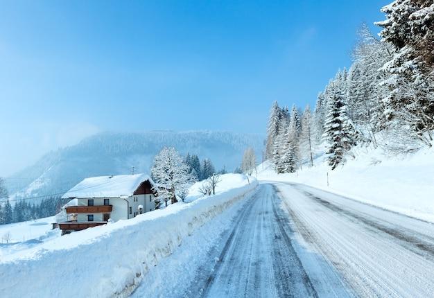 Poranna zima mglisty wiejski widok z alpejską drogą i domem na poboczu drogi.