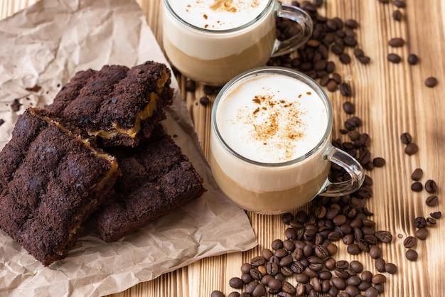 Poranne cappuccino z ciastem czekoladowym. na drewnianym stole z ziaren kawy.