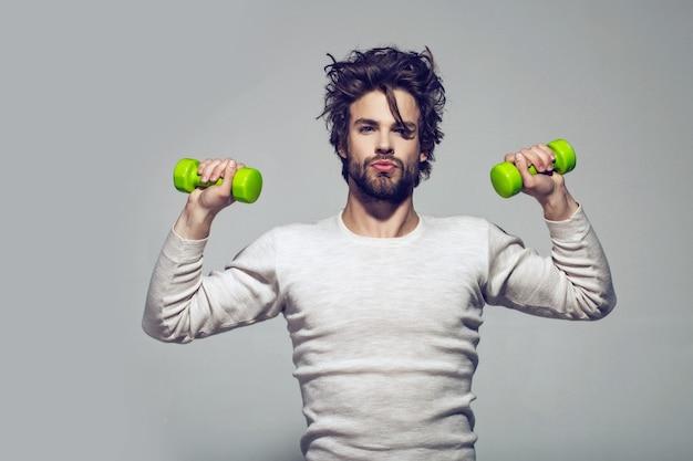 Poranne ćwiczenie mężczyzny ze sztangą ma nieuczesane włosy