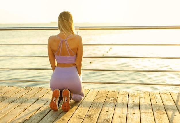 Poranne ćwiczenie. młoda sportowa kobieta w sportowej ćwiczy medytację siedząc na plaży i patrząc na wschód słońca. widok z tyłu