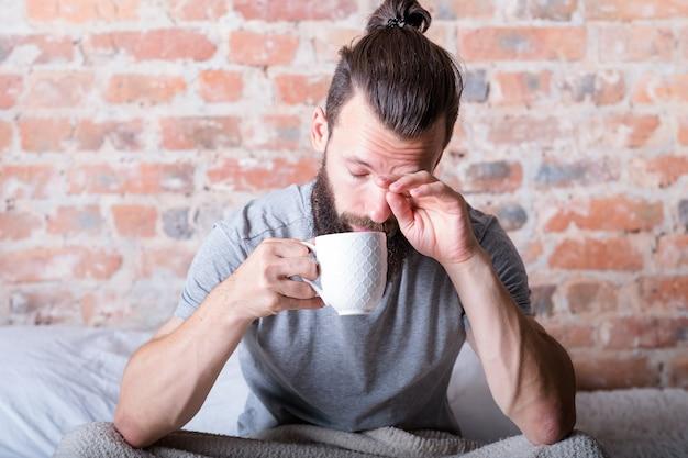 Poranne lenistwo. mężczyzna w łóżku pociera zaspane oczy. czas wstawać. kubek gorącego napoju w dłoni.