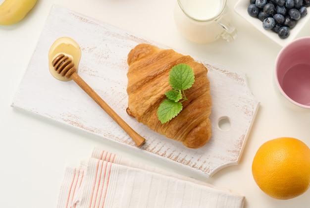 Poranne śniadanie, pieczony świeży rogalik, mleko w karafce, jagody i miód w słoiku na białym stole, widok z góry, miejsce na kopię