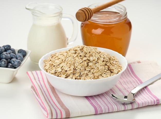 Poranne śniadanie, surowe płatki owsiane na talerzu ceramicznym, mleko w karafce i miód w słoiku na białym stole, zbliżenie