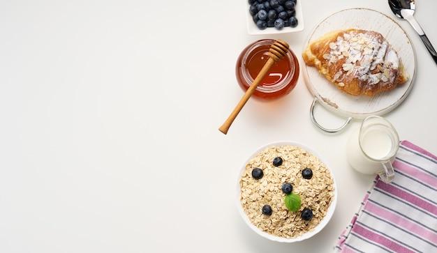 Poranne śniadanie, surowe płatki owsiane na talerzu ceramicznym, mleko w karafce, jagody i miód w słoiku na białym stole, widok z góry, miejsce na kopię