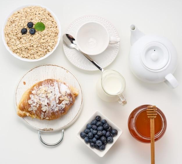 Poranne śniadanie, surowe płatki owsiane w ceramicznym talerzu, mleko w karafce, jagody i miód w słoiku na białym stole, widok z góry
