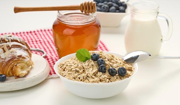 Poranne śniadanie, surowe płatki owsiane w ceramicznym talerzu, mleko w karafce, jagody i miód w słoiku na białym stole
