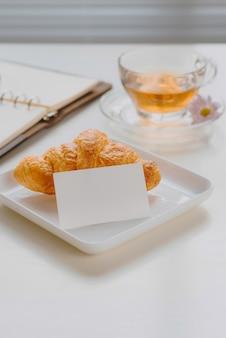 Poranne śniadanie w salonie z francuskim croissantem, filiżanką, długopisem i notatnikiem na kamiennym stole
