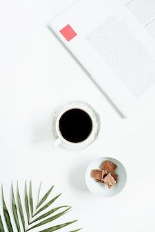 Poranne śniadanie z filiżanką kawy i czekoladą z tropikalnym liściem palmowym i magazynkiem na białym tle