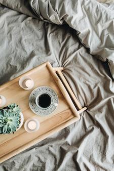 Poranne śniadanie z kawą do łóżka. kompozycja martwa natura leżąca płasko, widok z góry. drewniana taca i szary len.