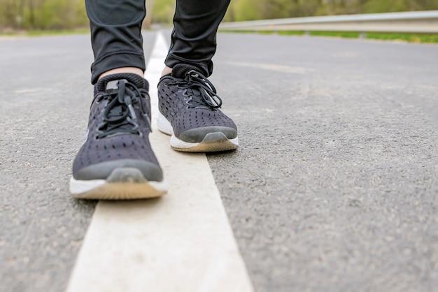 Poranny bieg. biegnące stopy podczas biegu, runner w czarnych tenisówkach biegnie po asfalcie.