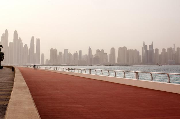 Poranny bieg, mężczyzna biegnie wzdłuż drogi z pięknym widokiem na dubaj. zea
