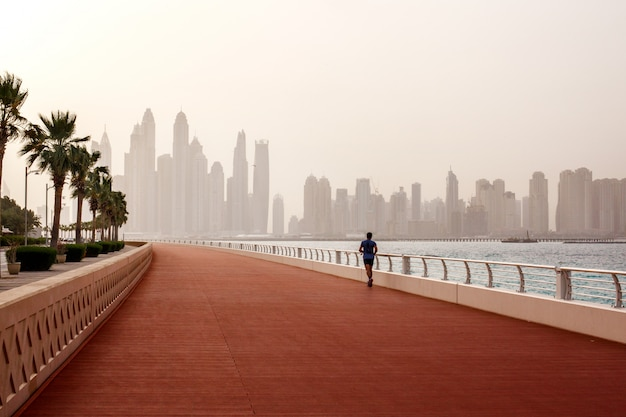 Poranny bieg, mężczyzna biegnie wzdłuż drogi z pięknym widokiem na dubaj.