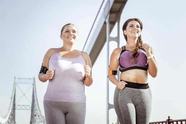 Poranny bieg. zachwycone pozytywne kobiety uśmiechnięte podczas wspólnego biegania o poranku