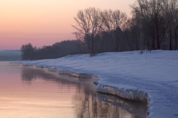 Poranny brzeg wiosennej rzeki zakrzywiony brzeg rzeki ob pokrywają niebieskie zaspy śnieżne