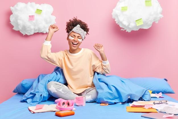 Poranny czas na naukę koncepcji relaksu. szczęśliwa kobieta w piżamie rozciąga ramiona siedzi skrzyżowanymi nogami
