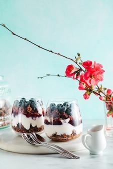 Poranny deser z granolą w szklance z jogurtem, dżemem i świeżymi jagodami.